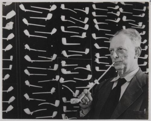 NL Gd SAMH 0440 52886 Een man rookt uit een lange pijp van de N V Goedewaagen Op de achtergrond het modellenbord met pijpen ca 1950